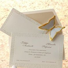 Partecipazione in cartoncino avorio con decorazioni in rilievo e perla.
