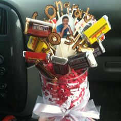 Graduation gift for young men!! A candy bar bouquet!!! Cut out letters of the name of graduate and a senior picture and attach to toothpicks. Fill a vase with Easter grass (school colors) and a piece of floral foam. Stick the letters into the foam. Attach miniature candy bars to toothpicks and arrange around letters. Add a bow and this is a great and delicious substitute for flowers!