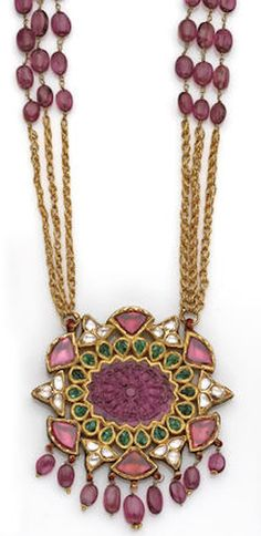 A Moghul style ruby, emerald, diamond and gold pendant necklace the openwork oval pendant centering a carved ruby of floral design within a frame of leaf-shaped emeralds and further surround of table-cut rubies and diamonds with edges of red enamel, suspending a ruby bead fringe, the reverse of similar design, completed by a three-strand fancy-link chain with ruby bead detail; length: 23½in. (loss to enamel)