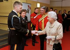 The Queen shakes hands with Captain Christopher Miorin of the US Army Rifle drill team, after watching his team in action at the British Military Tournament, at Earls Court in west London. Photo by John Stillwell/PA Wire PRESS ASSOCIATION.