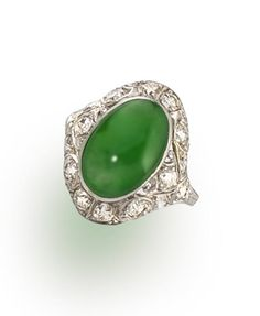 A jadeite jade and diamond ring  centering an oval cabochon jadeite jade, measuring approximately 8.4 x 13.0 x 5.2mm., within an intricate openwork mount of old European-cut diamonds; mounted in platinum