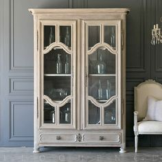 Beautiful 19th century French Oak Armoire with elegant, decorative glass front doors. The oak was softly washed in pale grey, gorgeous hand carved cabinet and unusual details make this extraordinary, a stunning addition to any room in your French Country home. Working key, 2 bottom drawers and 3 shelves provide lots of storage. This gorgeous armoire dates to 1850.        88H x 63W x 24D         Please only buy this if you adore antique and vintage furniture, this shows wear due to age, it's