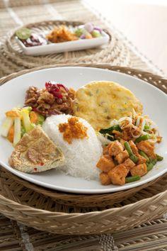 Nasi Kampung. Our nasi kampung is served with omelet, urap, tempe balado, bakwan jagung, pickles and toasted coconut.