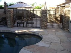 Like the stone accents for the fence  Stone patio, pool, BBQ island