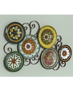 Italian Plates Wall Sculpture - A variety of floral designs on metal plates of varying sizes create a feeling of old Europe wherever you hang this Italian Plates Wall Sculpture. Each plate is hand-painted, then glazed before being mounted to a decorative scroll. Hang it vertically or horizontally to fit your space. Solutions.com