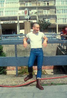 A teenage skinhead boy, wearing Doc Marten boots, Standing in the street, UK 1980's. ©Gavin Watson/PYMCA