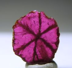 Ruby Trapiche- A gemmy trapiche slice of Ruby with well defined trapiche lines (six rays). It has beautiful raspberry red color and excellent clarity. From Burma.