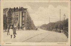 Haarlemmerweg hoek Wittenkade, tramrails, twee kinderen op brug 347. Op het trottoir veel mensen en rechts een kroonlantaarn. 1905-1915