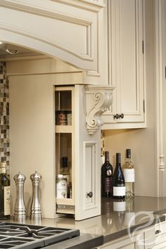 cream-colored custom cabinetry and range hood with corbels on both
