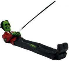 "Zombie ash catcher. A wonderfully macabe incense holder formed from a zombie in the classic coffin death pose ready to hold any incense stick. NOT for burning cone incense. 10 1/2"" x 2"" x 2"""