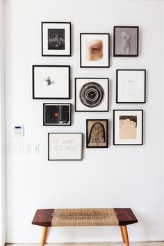 Above a wabi-sabi-style bench, a gallery wall of small-scale art (tied together by the black frames) lies just inside the entry. Works radiate from the central spiral ink drawing by Raymond Pettibon. Photos by Nicole Lamotte via One Kings Lane