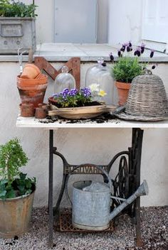 Old Cast Iron Sewing Machine base made into a planting table.old metal watering can, woven bee skep, clay pots, & flowers. Sewing Machine Tables, Old Sewing Machines, Sewing Table, Flea Market Gardening, Potting Tables, House Plant Care, Creation Deco, Plantation, Garden Pots