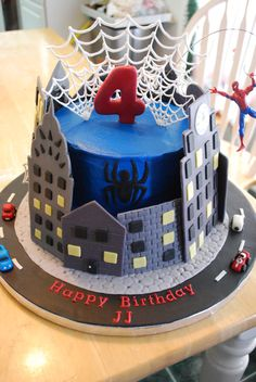 Spiderman Cake with fondant buildings and cars and royal icing spider webs.  TYFL!