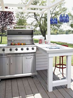 When space allows, add a countertop or island next to the grill to make food prep and service easier. A peninsula works well in this outdoor kitchen. It provides additional seating for outdoor dining that's close enough for the cook to chat with guests, b Simple Outdoor Kitchen, Outdoor Kitchen Design, Kitchen On A Budget, Kitchen Ideas, Kitchen Layouts, Small Outdoor Kitchens, Outdoor Kitchen Grill, Bbq Kitchen, Backyard Kitchen