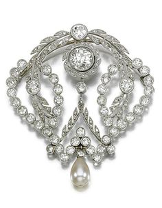 DIAMOND BROOCH.   Of open work design millegrain-set with circular- and rose-cut diamonds, the principal circular-cut diamond weighing 1.34 carats, suspending an articulated pearl drop, composite, later pin fitting, one small diamond deficient. Edwardian or Edwardian style.