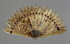 Tortoiseshell brisé fan in the Gothic Revival style, gilded and painted.  Probably English c1820-1820. Fitzwilliam Museum