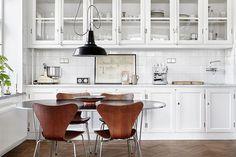 ÖSTERLEN -- eat-in white kitchen, glass cupboard doors, mcm Danish dining set, industrial pendant