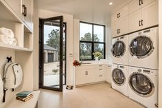 Clean, white mud room with double washer and dryer | Clarum Homes