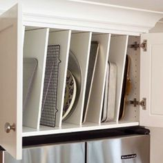 Everyone has those odd-sized cabinets above their refrigerator. How about using them to organize your baking sheets and large platters? Install dividers and use the space to store flats in #kitchen.