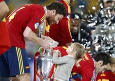 Spain's Xabi Alonso and a child celebrate with the trophy after defeating Italy to win the Euro 2012 final soccer match at the Olympic stadium in Kiev, July 1, 2012.