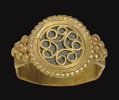 A BYZANTINE GOLD FINGER RING   CIRCA 5TH-6TH CENTURY A.D.   The wide faceted hoop with a granulated triangle on each shoulder, the circular bezel enclosing a steatite disk, inscribed with symbols on the underside, the upper surface enclosed within a beaded border, and covered by four openwork volutes