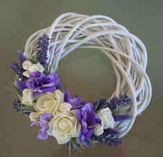 Bílý proutěný věneček do fialkova Bílý proutěnývěneček vbílých a fialkovýchodstínech na bílém proutěnémkorpusuo průměru25 cm, zdobenýlátkovými květy a pěnovými růžičkami,umělou levandulí,ratanovými kouličkami asušinou.