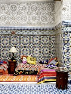 Layers of pattern and color are typical of Moroccan design. Here we see mosaic zellij Moroccan tiling on the lower part of the walls with a different border. The upper part of the walls are covered in sculpted geps or plaster of paris.