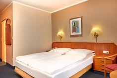 Blick auf das Doppelbett in einem der Kofortzimmer im H+ Hotel Lampertheim
