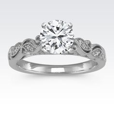 Swirls of vintage-inspired vine detailing wrap around this breathtaking engagement ring crafted of superior quality platinum. Twelve round diamonds, at approximately .05 carat total weight, provide ample brilliance to the design in addition to milgrain detailing. This engagement ring measures 3mm wide and waits to be completed by the center diamond of your choice.