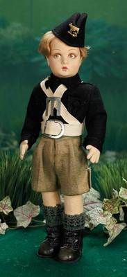 Marks: (original Lenci paper label). Comments: Lenci, circa 1930s. Value Points: near pristine condition, the little boy wears black felt shirt and cap with embroidered emblem, white felt belt and sash, grey felt shorts, woolen stockings and leather ankle boots.