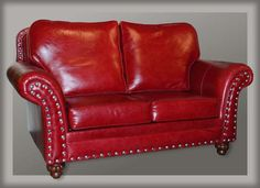 Wild Horse Saloon Western Loveseat Western Sofas and Loveseats - Beautiful crimson red leather upholstered this Western style loose back loveseat. Eye catching details are added, like antique silver nail head trim and top stitching on the arms. Made in the USA.
