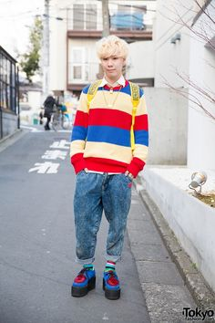 """Seiya is wearing a striped sweater over a white shirt, with rolled up acid wash jeans, all of which are resale purchases. His colorful backpack is from Lipano and his creepers are Underground, worn with striped socks. His accessories include items from Dior, Ambush (the """"POW!"""" necklace), and RNA."""