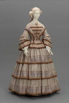 1855 - robe deux pièces - Elle a un corsage très long sur une jupe à volants - elle est réalisée en soie tissée et chaque volant est orné de franges.  Victoria et Elizabeth