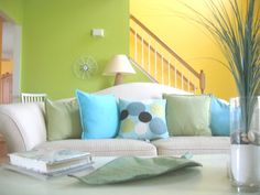 This cheery living room is decorated bright cool colors. The combination of light blue, lime green, and bright yellow make the room feel happy.  http://www.walldesignideas.net/2011/08/25/room-wall-color/