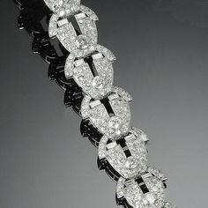 An art deco diamond bracelet, by Cartier, circa 1930 Designed as series of openwork shield-shaped links, pavé-set with old brilliant-cut diamonds and baguette-cut diamond highlights, diamonds approximately 14.60 carats total, signed Cartier London, length 17.3cm., fitted case