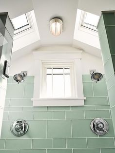 idea for an attic bathroom remodel/addition: To get the feel of an outdoor shower in this master bath, the owners installed two skylights and tile that mimics the look of sea glass.  LOVE this!