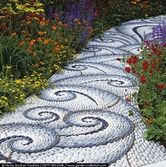A magnificent pebble mosaic path by Maggy Howarth, edged in geum, catmint, achillea, poppies & potentilla.  (She has a book called The Art of Pebble Mosaics.)