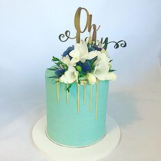 Teal blue baby shower cake featuring a gold drip and fresh flowers.