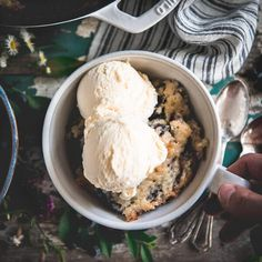 """This easy blueberry cobbler is a delicious way to enjoy fresh summer berries! The cake-like batter puffs up around the fruit, giving the dish that classic """"cobbled"""" texture on top. It's warm, buttery, soft in the center, and crisp on the edges -- thanks to the magic of a cast iron skillet. Serve the old fashioned blueberry cobbler with a scoop of vanilla ice cream for a simple Southern dessert! During the warm summer months, you can't beat a rustic dessert that takes advantage of fresh…"""