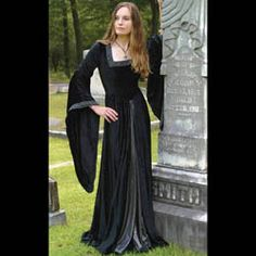 http://www.medievalcollectibles.com/p-922-black-countess-dress.aspx - This full-length, black crushed cotton velvet gown is cut in the courtly tradition of the late middle ages. Both the bell-cut sleeves and square-cut neckline are trimmed with a silver floral pattern, encrusted with dark jewels. The open cut front is lined with a dark silver lamme, while the easy lace-up back ensures a stunning, shapely fit every time. $169.00