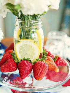 Carnations in a canning jar, with fresh lemon slices surrounded by strawberries. Love this for Mother's Day brunch.
