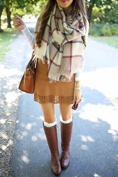 Plaid scarf, and white sweater, tan leather skirt, brown boots with knee high socks