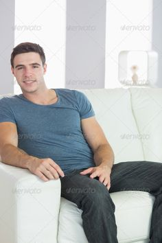 Smiling handsome casual man relaxing on couch in bright living room ...  20s, Abode, Looking At Camera, Short Hair, apartment, attractive, brown hair, brunette, casual, caucasian, cheerful, content, couch, denim, domicile, handsome, happy, home, homey, house, household, indoors, jeans, leisure, lifestyle, living room, male, man, portrait, relaxing, sitting, sitting room, smiling, sofa, tshirt, young adult
