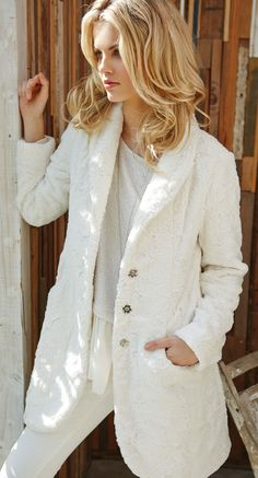 Plush faux fur brings cozy warmth to a long straight coat with a foldover collar.