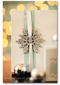glitter snowflake gift wrapping, and you can use the snowflakes from the dollar store!