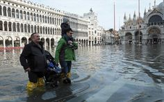 Men carry children through a flooded St. Mark's Square during a period of seasonal high water in Venice Wooden Walkways, High Tide, Natural Phenomena, New Life, Places To Travel, Venice, Louvre, Boat, City