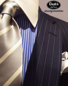 "A lighter shade navy rope-stripe in a soft silver wool/cashmere blend by Holland & Sherry. Custom Made ""Off the Rack"" as an updated version of the old ""navy pinstripe."" The shirt is an Albini 2-Ply Egyptian cotton Custom Made ""Off the Rack"" in soft cobalt blue and white stripes in perfect scale to complement the suit. The soft silver in the tie complements the silver shade of the suit and the white gives depth and pulls everything else together, so one thing does not ""out shine"" everything…"