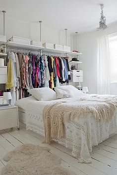 If you don't have a closet, use DIY shelving to hang clothes in place of a headboard for a chic loft look.