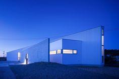 位於徳島県小松島市的木造平屋,這是建築師 岸本貴信 的設計作品,基地位於三面環海的半島地形中,經常面臨強風和夏日颱風的侵襲,因此130坪的廣闊面積決定以水平方式開展,透過建物的面向與兩端尖角減低強風的影響,純白簡約的空間感有利於周圍景色的馴染,創造最高的投射效果。  via CONTAINER DESIGN