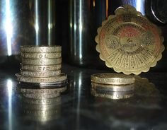 """Stack of coins , with """"money"""" lined vertically alongside a miniature calendar which lasts for 36 years . Experimenting with camera , can't do anything outside . Please try large view .     http://www.maxonking.8m.com"""